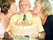 Man Blowing Candles on Cake with Two Women
