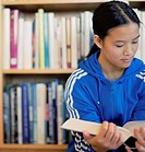 Teenager Reading Book in Library