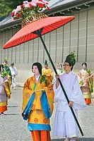 A costumed couple are walking in the parade for the Aoi Matsuri, with the man holding a large red umbrella over the woman
