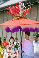 A costumed couple are walking in the parade for the Aoi Matsuri, under a large umbrella that the man is holding over the woman