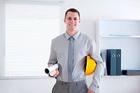 Architect carrying helm and plans in his office