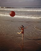 Young woman playing with beach ball on beach