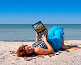 Woman with laptop at sea coast