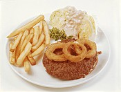 Roasted meat with French fries, onion ring and cabbage on plate