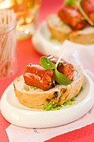 Chorizo cooked in white wine on a slice of bread