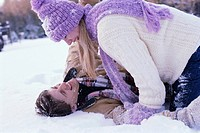 Woman Smiling at Man Lying in Snow