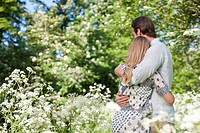 Couple hugging in field of flowers (thumbnail)