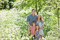 Family standing together in field of flowers