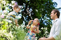 Family playing with bubbles outdoors