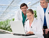 Scientists working on laptop in greenhouse