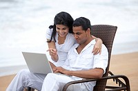 Couple with a laptop at a beach