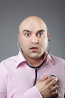 Man using a stethoscope to check his heart rate