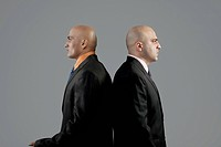Two bald businessmen standing back to back