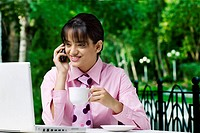 Businesswoman drinking coffee while using cell phone and laptop at cafe