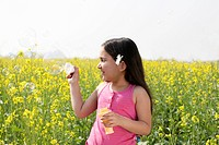 Young girl making bubbles in a field