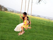 Mother and daughter having fun on a swing