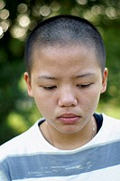 Sad asian teen girl with shaved bald head