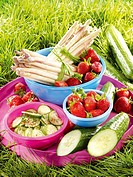 Fruit and vegetables on a tray in the grass