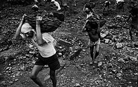 Miners carry away basket loads of coke cooled by water for loading into coal wagons at an open cast mine at Dhanbad. These miners transport up to thre...