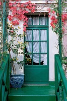 A doorway into Monet´s house painted geranium green and dappled with climbing plants.