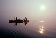Two men paddle their canoe across a foggy lake at dawn in the Northwest Territories, Canada.