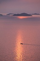 The evening sun sets behind a small fishing skiff among the islands west of Molde, on Norway´s west coast.
