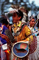 A native American teenage boy wears traditional tribal clothing during a Pow Wow.