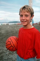 A boy holds a ball on the beach in Ischia, Italy.