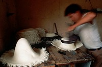 A hat maker shapes, blocks, and irons a Montecristi Panama hat made of stripped and dried paja toquillo palm fronds.