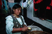 Mrs. Cushcagua peels potatoes while standing beneath clotheslines covered with drying laundry. Otavalo, Imbabura, Ecuador.