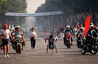 A wheelchair athlete and marathon runners sprint for the finish line during the Ho Chi Minh International Marathon in Ho Chi Minh City, Vietnam.