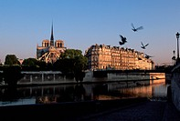 A quay leads down to the Seine river where evening light shines on the water and the buildings of Isle de la Cite above. Paris, France.