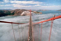 Michael Scott walks above a fog bank on one of the high cables holding up the Golden Gate Bridge. He paints the bridge´s cables.