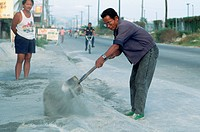 Filipinos in masks sweep volcanic ash from the streets near Clark Air Force Base. This cleanup has been an everyday event since the eruption of Mount ...
