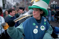 A woman wears a St. Patrick´s Day hat and drinks from a large beer glass during the St. Patrick´s Day Parade in downtown Chicago. Illinois.
