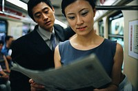 Businesspeople Reading Newspaper on Subway