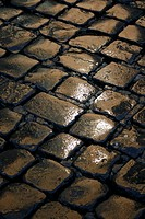 wet pavement cobbles in rain at night