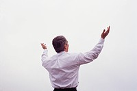 Businessman Reaching Towards the Sky