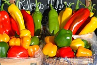variety of peppers, some long, some more apple-shaped, red, yellow, orange and green, with chalkboard behind, at farmers' market