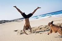 Young Man Cartwheeling on Beach