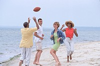 Two couples playing with a football on the beach