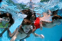 Children Swimming Together Underwater
