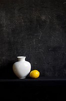 white vase and lemon on black background