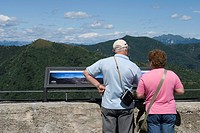 Couple of tourists watching mountain landscape from Sacro Monte of Varese, Lombardy, Italy