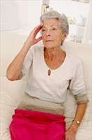 ALZHEIMER, senior woman holding her forehead and trying to remember her souvenirs