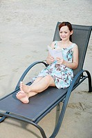Woman sitting on beach chair reading book