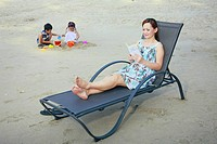Woman sitting on beach chair reading book, boy and girl playing with sand in the background