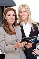 Two smart women in business or businesswomen outside using a tablet computer or iPad