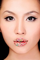 Woman with candy sprinkles on lips