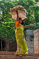 Female fruit seller carrying a basket of pineapples on head, Hampi, Karnataka, India